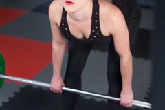 Sexy woman flexing muscles with barbell in gym.  Stock Image