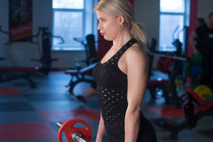 Sexy woman flexing muscles with barbell in gym.  Stock Photography