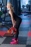Sexy woman flexing muscles with barbell in gym Royalty Free Stock Images