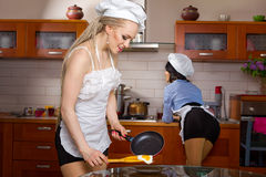 Sexy woman frying eggs Stock Images