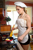 Sexy woman frying eggs Stock Photo