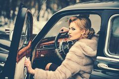 Sexy woman in fur coat. Call girl in vintage car. Travel and business trip or hitch hiking. Retro collection car and. Auto repair by driver. Escort and security royalty free stock images