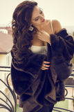 Sexy  woman in fur coat posing at the balcony Stock Image