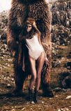 Sexy woman with fur hood on head with bear. On nature Royalty Free Stock Photos