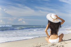 Woman Girl Sitting Sun Hat & Bikini on Beach. A young brunette woman or girl wearing a white bikini and sun hat sitting on a deserted tropical beach with a blue royalty free stock photography