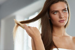Woman With Haircomb In Hand Hairbrushing. Hair Health Stock Photo