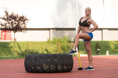Sexy Woman With Hammer And Tire Royalty Free Stock Images