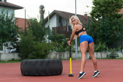 Sexy Woman With Hammer And Tire Stock Images