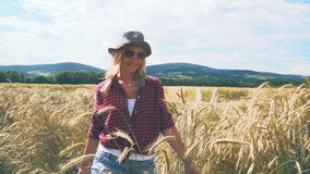 Sexy woman with hat and short jeans goes through rye field