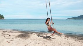 Sexy woman having fun swinging at tropical beach stock video