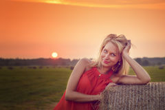 Sexy woman on hay stack on sunset. Royalty Free Stock Photography