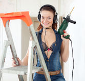 Sexy woman in headphones with drill Royalty Free Stock Images