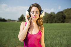 Sexy woman with headphones outside Stock Photography