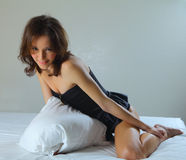 Sexy woman on her bed holding a pillow Stock Photography