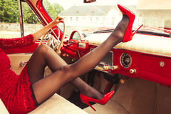 Sexy woman in high-heals sitting in retro car Stock Photo