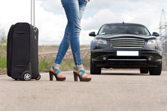 Sexy woman hitchhiking with her luggage. Low angle view of the sexy slender legs in high heels of a woman hitchhiking with her luggage stepping into the road to Royalty Free Stock Images