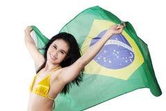 Woman holding Brazil flag in studio. Beautiful young woman holding Brazil flag wearing bikini. isolated on white stock photo