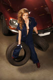 A sexy woman holding car tires in a garage Stock Image