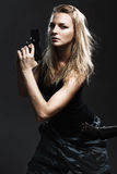 Sexy woman holding gun. On gray Stock Photo