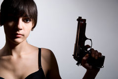 Sexy woman holding gun on gray Stock Images