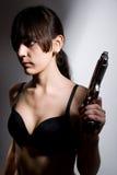 Sexy woman holding gun on gray Stock Photos