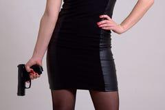 Sexy woman holding gun over grey Royalty Free Stock Photos