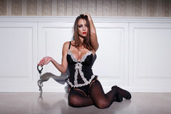 Sexy woman holding handcuffs at vintage wall Stock Images