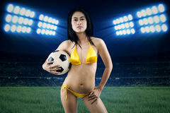 Sexy woman holding soccer ball at field Royalty Free Stock Photos