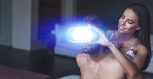 Woman holding VR glasses for man at night. Women holding VR glasses for men at night, cybersex stock photography