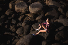 woman in jeans overall and pink t-shirt sit on big stone at rock beach sea ocean shore. Modern hipster girl have Royalty Free Stock Photos