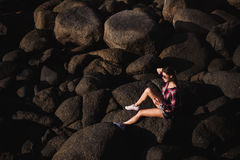 woman in jeans overall and pink t-shirt sit on big stone at rock beach sea ocean shore. Modern hipster girl have Royalty Free Stock Image