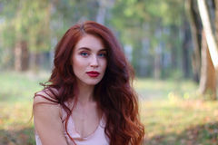 Sexy woman in jersey poses in autumn forest Royalty Free Stock Photos