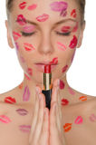 Sexy woman with kisses on face holding lipstick Royalty Free Stock Photos