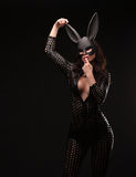 Sexy woman with large breasts wearing a black bunny mask standing on dark background and looks very sensually. Royalty Free Stock Image