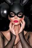 Sexy woman with large breasts, wearing a black mask Easter bunny Royalty Free Stock Photography