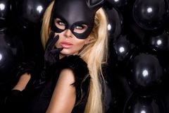 Sexy woman with large breasts, wearing a black mask Easter bunny Stock Image
