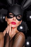 Sexy woman with large breasts, wearing a black mask Easter bunny Royalty Free Stock Images