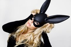 Sexy woman with large breasts wearing a black mask Easter bunny standing on a white background Royalty Free Stock Image
