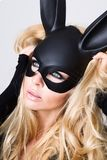 Sexy woman with large breasts wearing a black mask Easter bunny standing on a white background Stock Photo