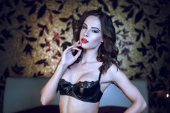 Sexy woman in latex bra in bedroom Stock Image
