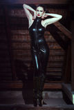Sexy woman in latex catsuit posing on timber Royalty Free Stock Image