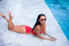 Sexy woman laying and relaxed near pool at cool black fashionable sunglasses,bra bikini pans, tan glowing skin woman. Amazing hairstyle, long hair style Royalty Free Stock Image