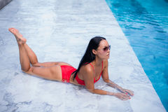 Sexy woman laying and relaxed near pool at cool black fashionable sunglasses,bra bikini pans, tan glowing skin woman. Amazing hairstyle, long hair style Royalty Free Stock Images