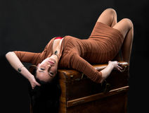 Sexy woman laying on a wooden chest Stock Image