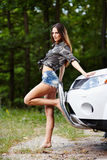 Sexy woman leaning on a car Stock Images