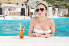 Sexy Woman Leaning on the Edge of Swimming Pool Stock Photography