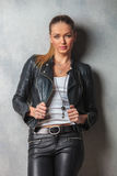 Sexy woman in leather clothes pulling her collar. And looks at hte camera in studio Stock Photo