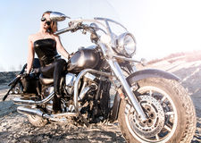 Sexy woman in a leather clothes sitting on a bike Stock Photos