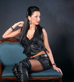 Sexy woman in leather clothing. Sitting on a chair Stock Photo