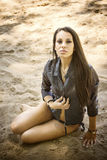 Sexy woman in a leather jacket sitting on the sand Stock Images